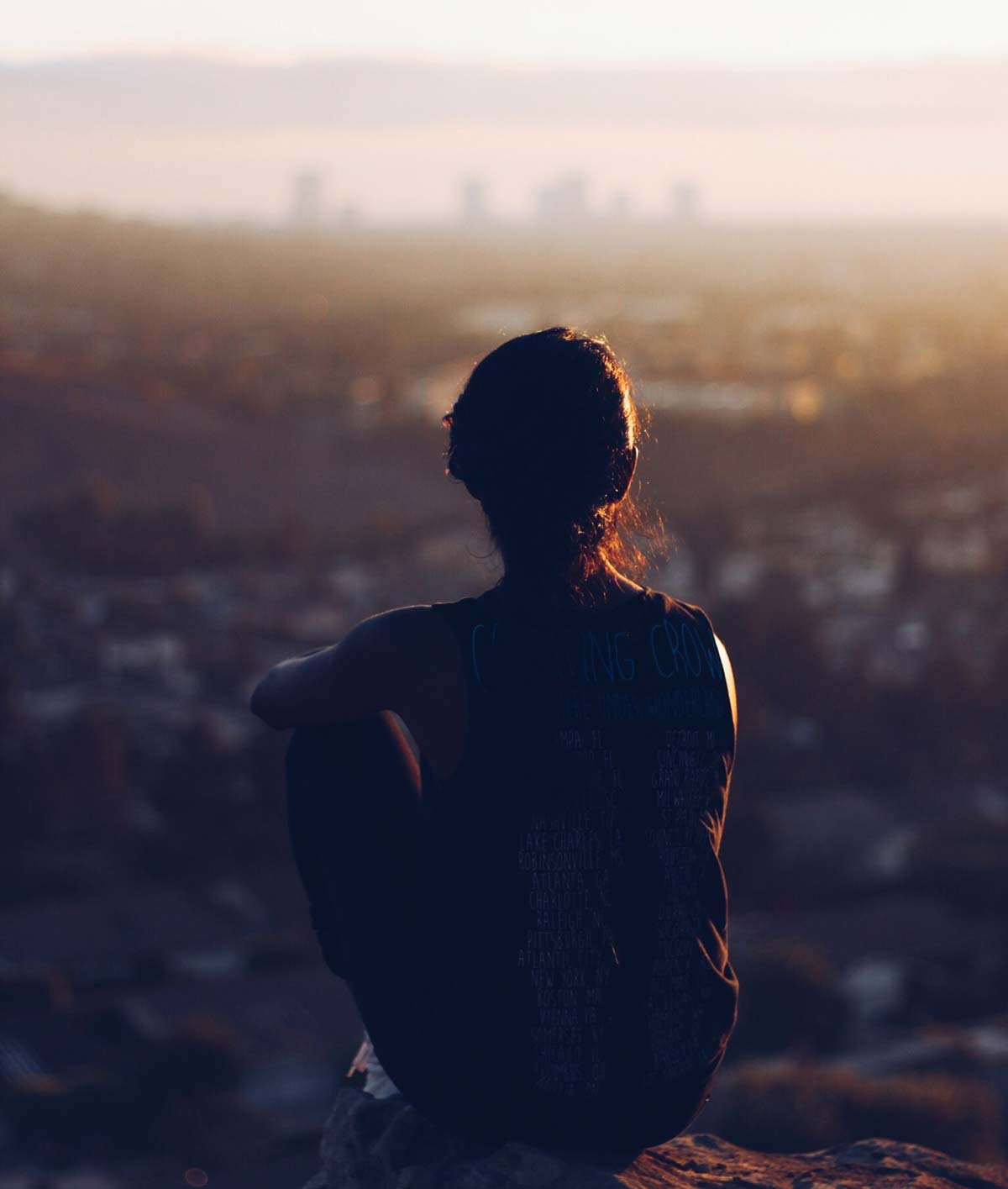 Girl sitting on rocks looking over city